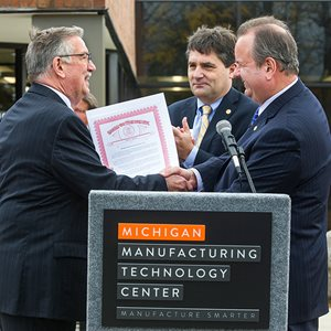 Michael Coast (left) receives a tribute from State Senator Patrick Colbeck, State Representative Kurt Heise (right).